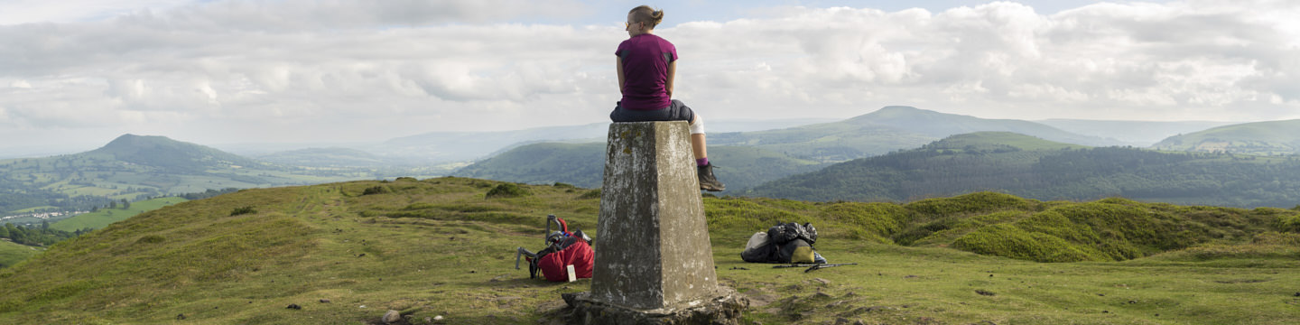 Hollie sits on a trig point in the Brecon Beacons