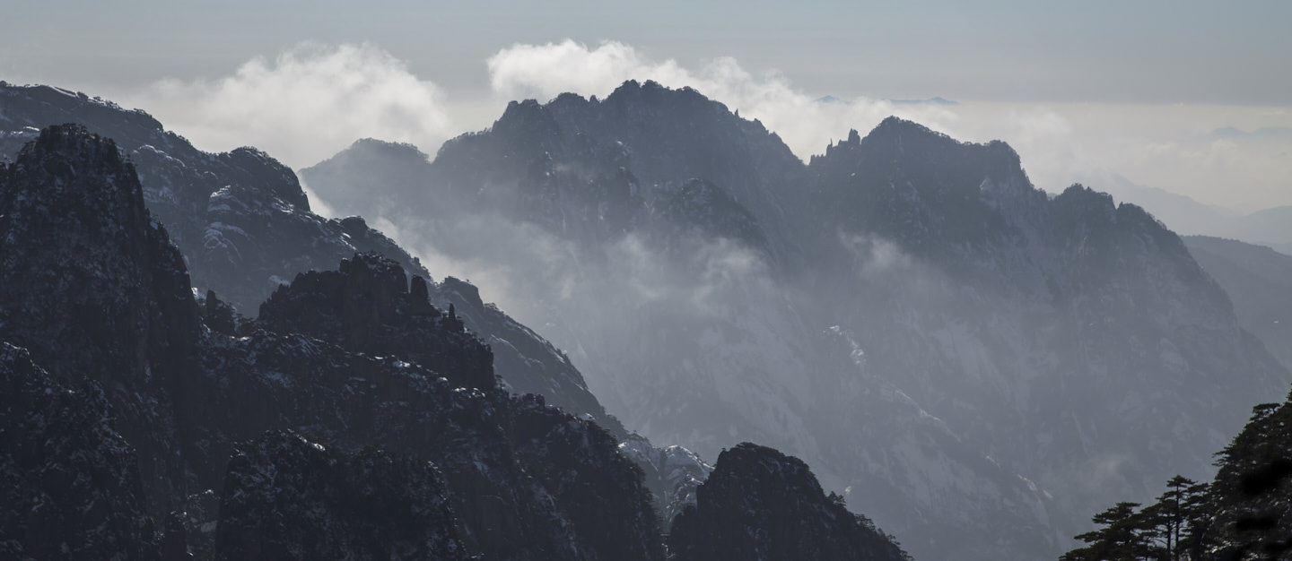 Cloud drifts below a jagged mountainscape
