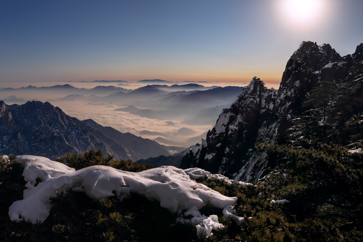 The sun rises over snow-topped peaks and the sea of clouds near Bright Peak
